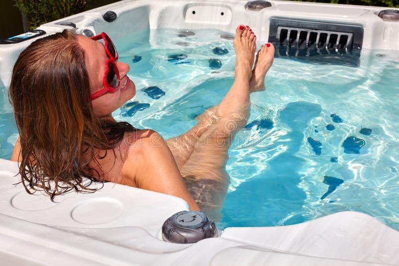放松在浴盆的美丽的妇女 免版税库存照片