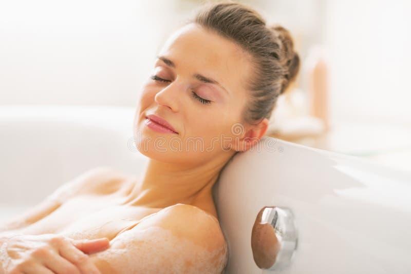 放松在浴缸的愉快的少妇 免版税库存照片
