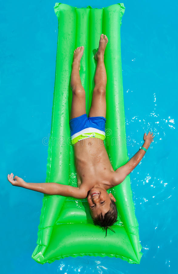 放松在绿色可膨胀的床垫的愉快的男孩 库存照片