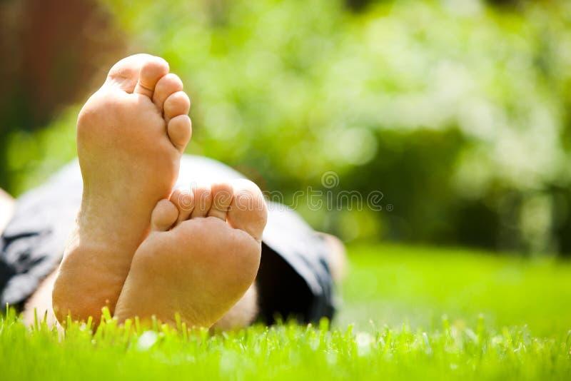 放松在绿草的人 免版税库存照片