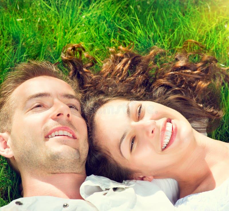 放松在绿草的愉快的夫妇 库存照片