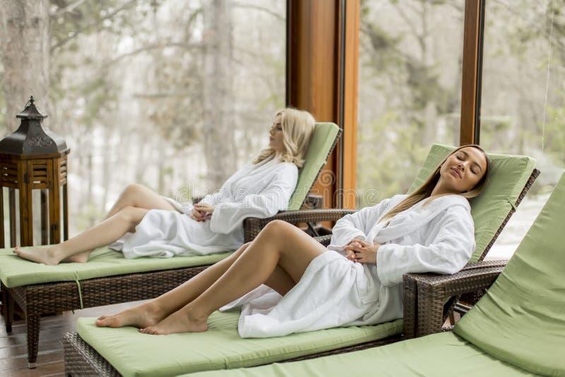 放松在deckchair的年轻女人由温泉的游泳场 库存照片