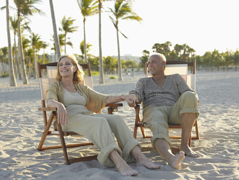 放松在Deckchairs的资深夫妇在海滩 免版税库存图片