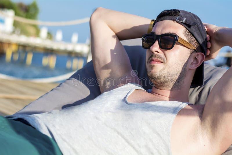 放松在sunbed和看蓝色海的年轻英俊的人 免版税图库摄影