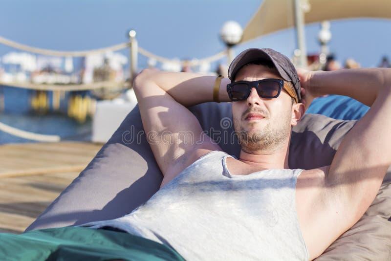 放松在sunbed和看蓝色海的年轻英俊的人 免版税库存照片