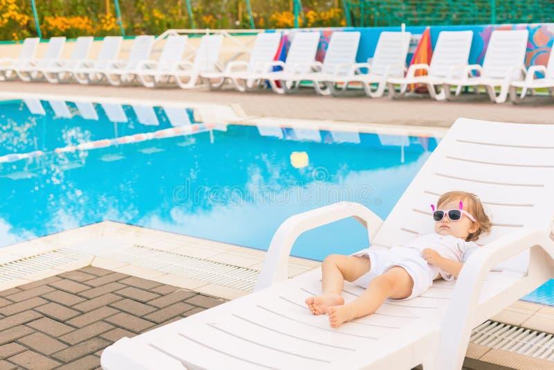 放松在sunbed的逗人喜爱的婴孩在水池附近在夏威夷,旅馆 图库摄影