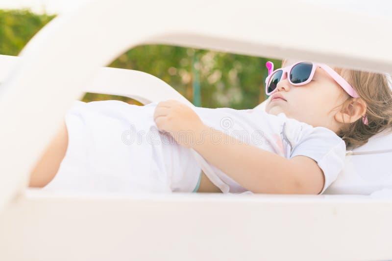 放松在sunbed的逗人喜爱的婴孩在水池附近在夏威夷,旅馆 库存照片