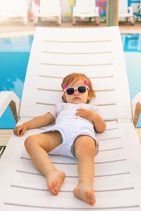 放松在sunbed的逗人喜爱的婴孩在水池附近在夏威夷,旅馆 免版税库存图片