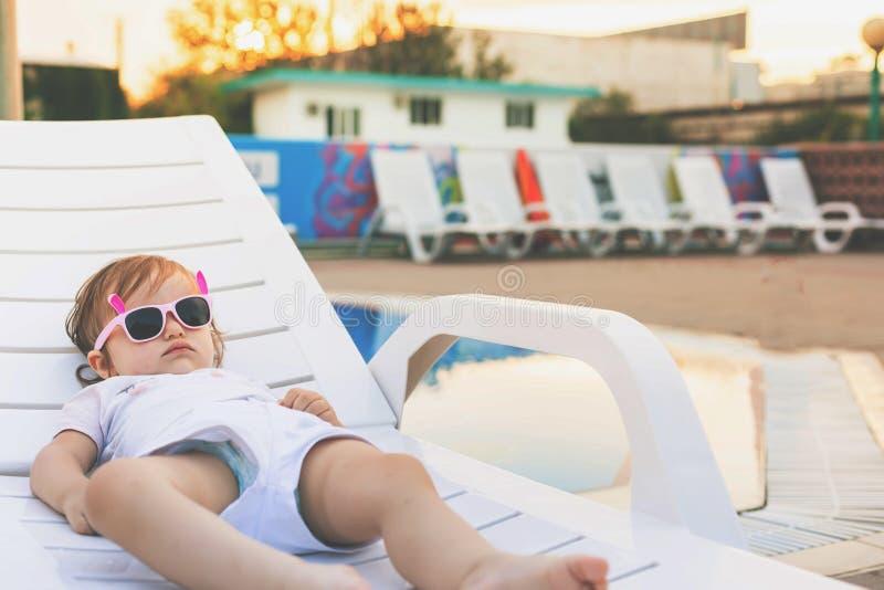 放松在sunbed的逗人喜爱的婴孩在水池附近在夏威夷,旅馆 免版税图库摄影