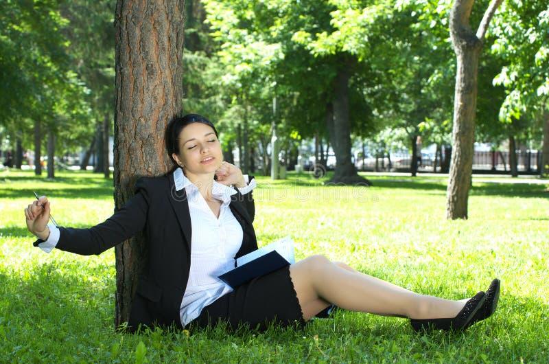 放松女实业家的公园 免版税库存图片