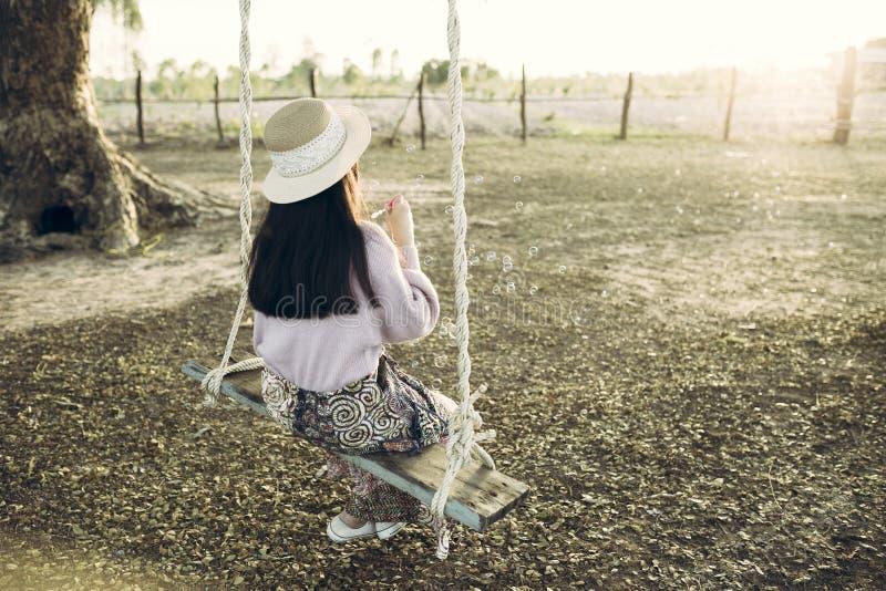 放松妇女喜欢吹泡影在树下 免版税库存照片