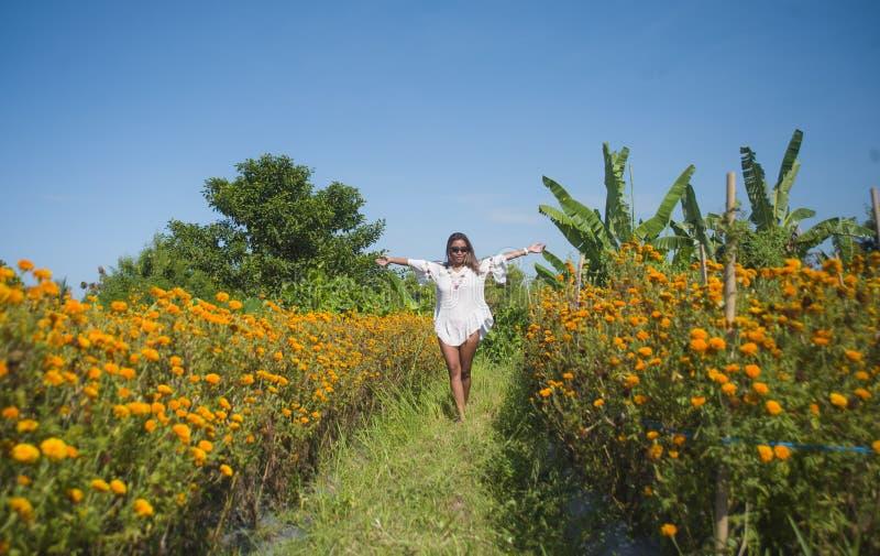 放松愉快和美丽的年轻亚裔的妇女享受华美的橙色万寿菊花田自然landsca新秀丽  库存图片