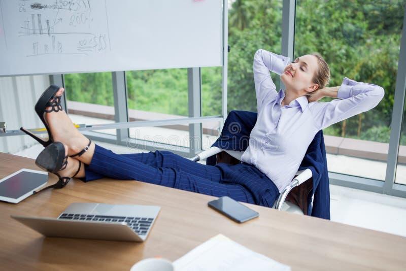 放松或睡觉与她的在书桌上的脚的女商人在办公室 女性上司工作者接近的眼睛与腿坐 库存照片