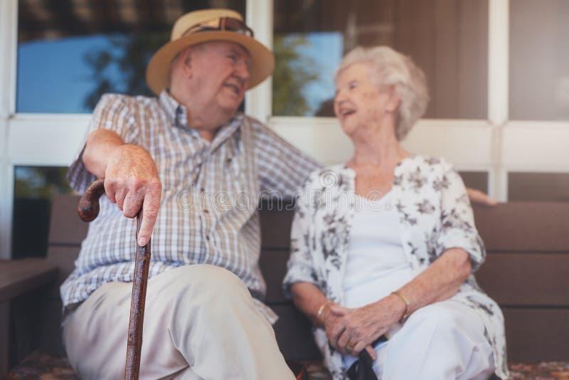 放松户外在长凳的爱恋的年长夫妇 免版税库存照片