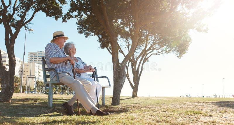 放松户外在长凳的退休的夫妇 免版税库存照片
