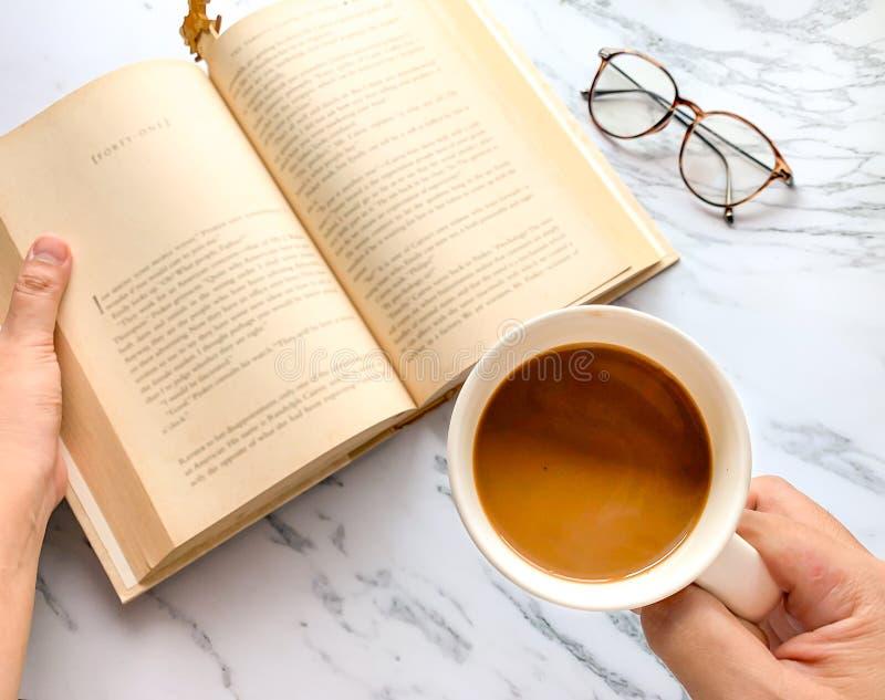 放松时间,左手拿着拿着咖啡杯的一只小说和右手 免版税库存图片