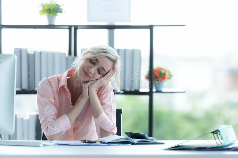放松时间 在现代办公室里勤恳工作后,成功的女商人放松休息 免版税图库摄影