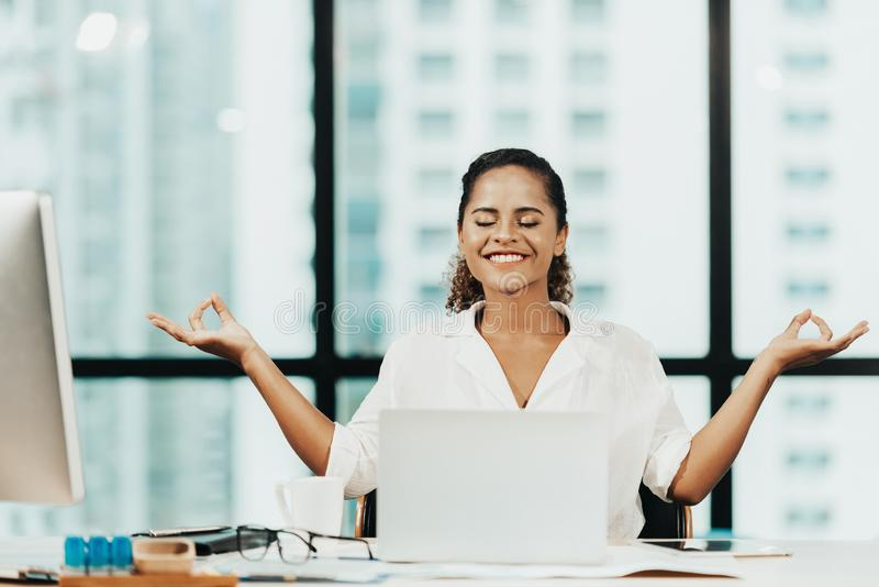 放松时间 放松和思考在现代办公室,记住平安和practici的努力以后的成功的女商人 免版税库存照片