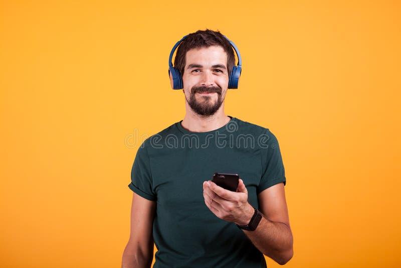 放松有蓝色耳机和智能手机的可爱的人在他的手上 免版税库存照片
