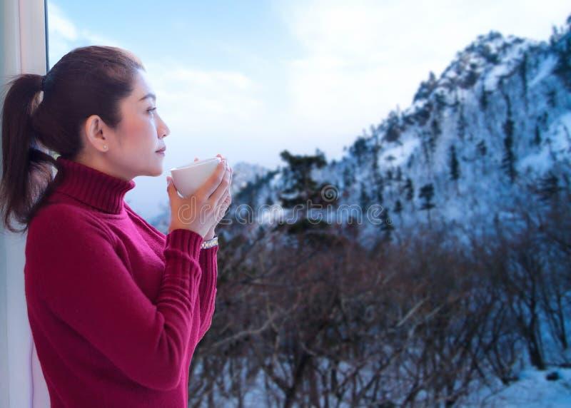 放松样式 与红色毛线衣新早晨喝热的咖啡和看窗口的亚裔妇女为看在的雪冬天 免版税库存图片