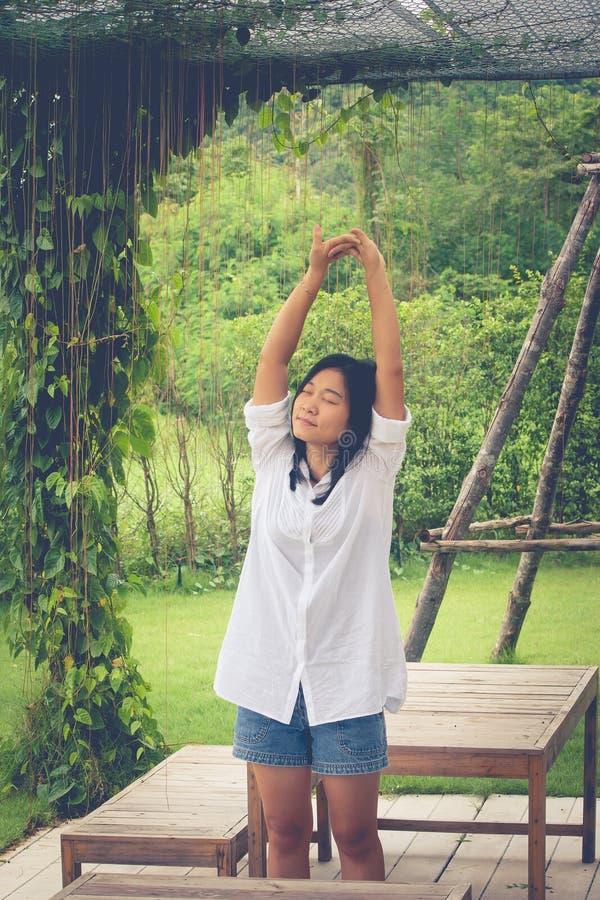 放松概念:亚洲女服白色衬衣和舒展在庭院里 免版税库存照片