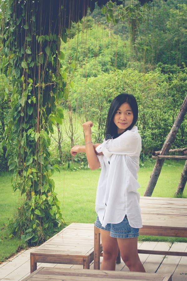 放松概念:亚洲女服白色衬衣和舒展在庭院里 图库摄影