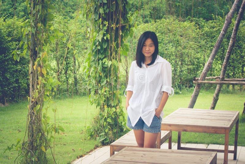放松概念:站立在草的亚洲女服白色衬衣在室外庭院 库存图片