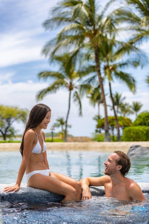 放松温泉渡假胜地的夫妇享受极可意浴缸浴盆游泳场户外在暑假旅行假日蜜月逃走 免版税图库摄影