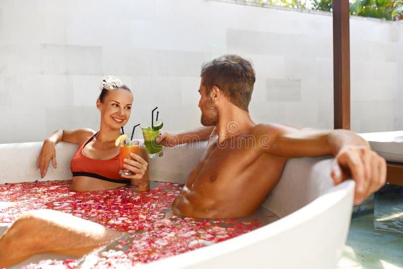 放松温泉 在爱的夫妇在花巴恩饮用的饮料 免版税库存图片
