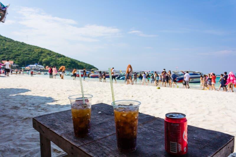放松用共同可乐和看见美丽的海滩 免版税库存图片