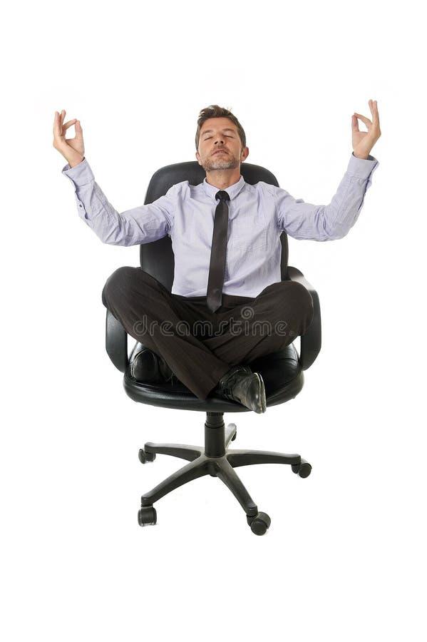放松用在瑜伽位置的手的年轻可爱的愉快的商人坐办公室椅子 图库摄影