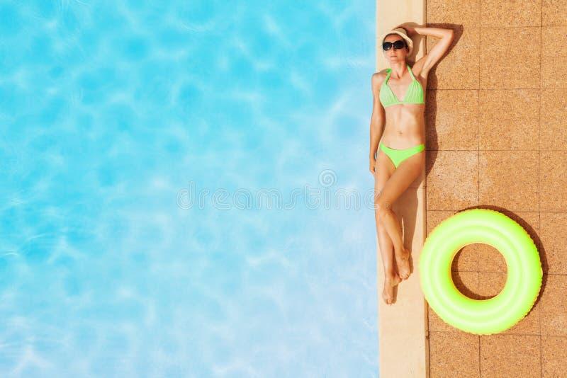 放松由游泳池的泳装的少妇 免版税库存照片