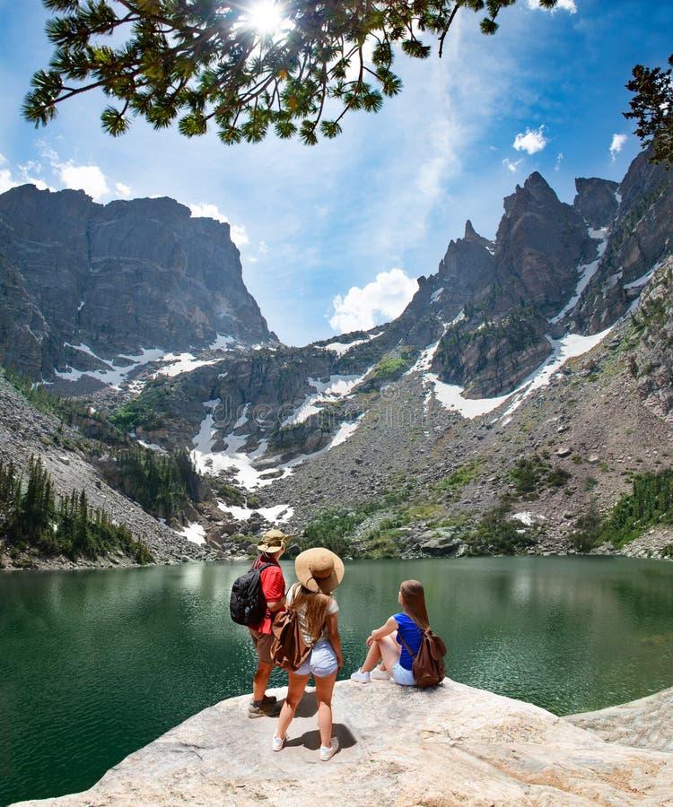 放松由湖的家庭,享受美丽的景色 免版税库存照片