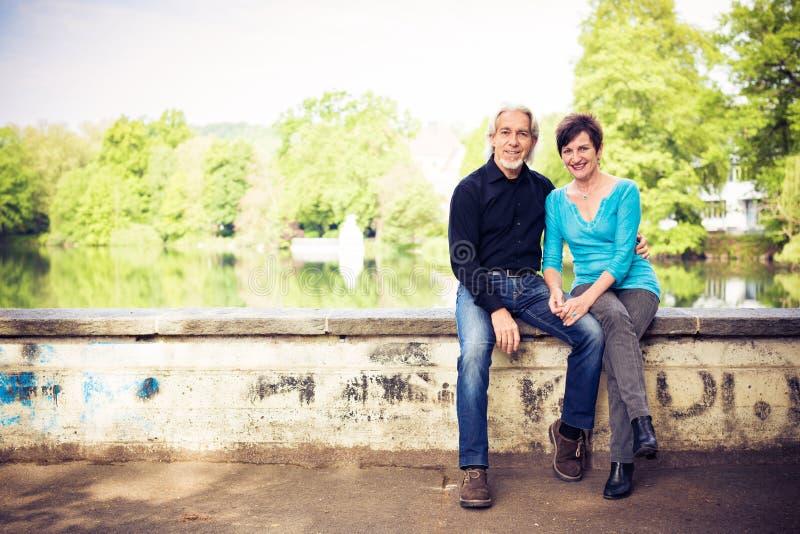 放松由湖的资深夫妇 库存照片