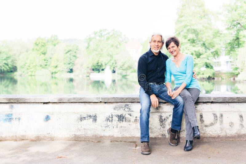放松由湖的资深夫妇 库存图片