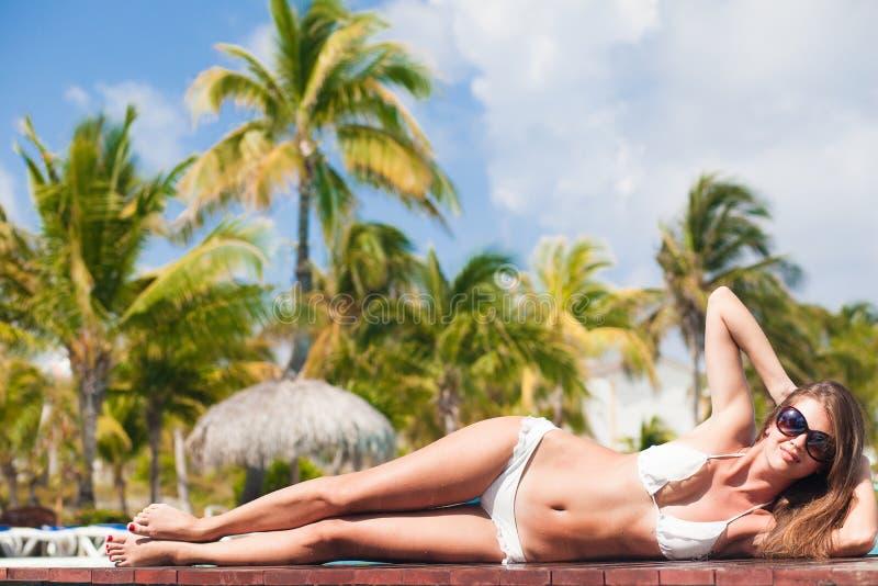 放松由热带水池的少妇 免版税库存照片