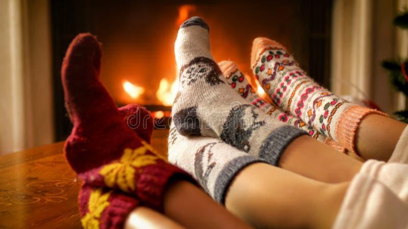 放松由自圣诞前夕的壁炉的家庭的被定调子的图象 免版税库存照片
