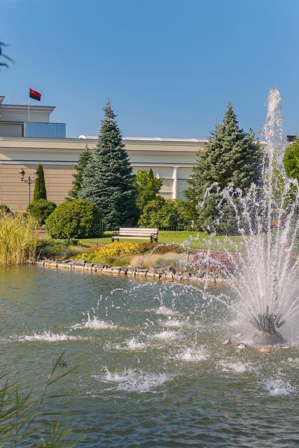 放松的一条长凳在池塘附近有喷泉的美丽的景色在水和美好的自然的 免版税库存图片