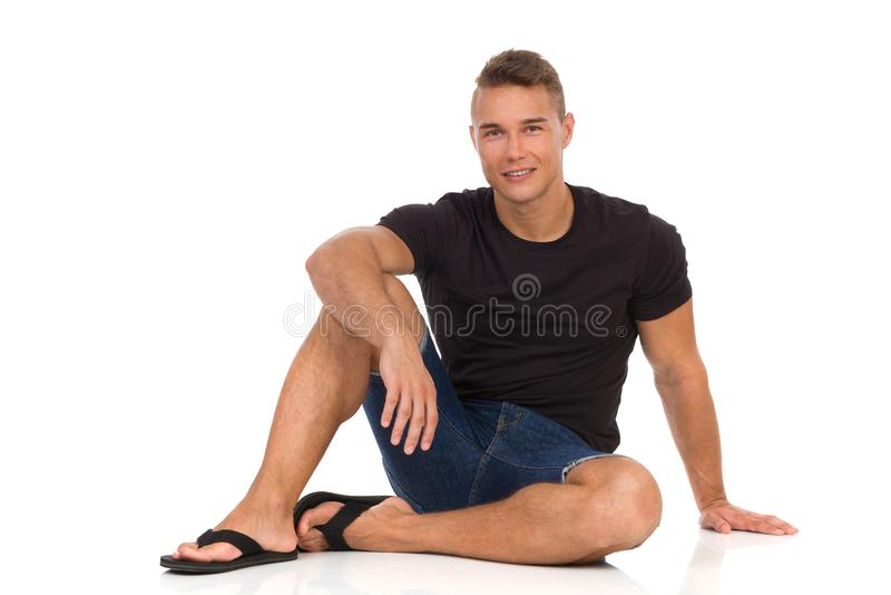 放松的人坐地板和微笑 免版税库存图片