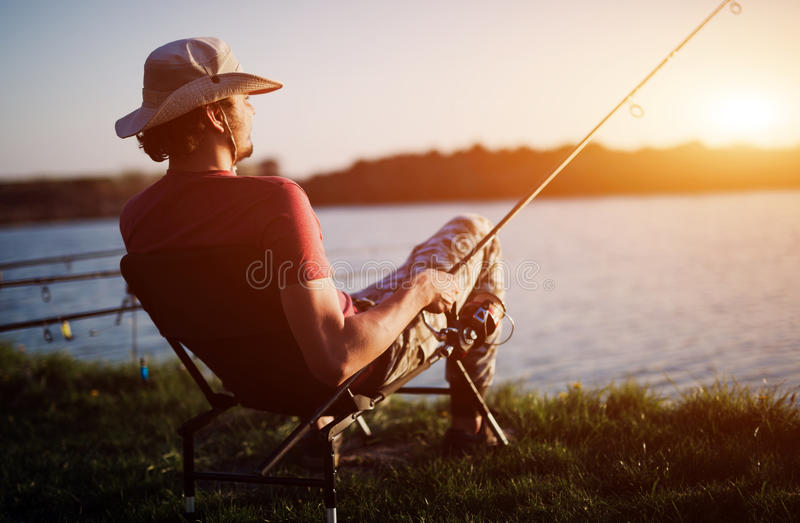 放松的人钓鱼在日落和,当享受爱好时 库存图片