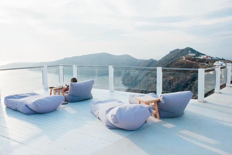 放松的地方与俯视海和山在圣托里尼的蓝色软的扶手椅子 免版税库存照片