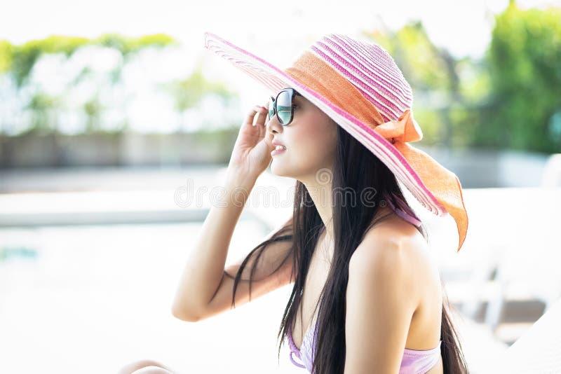 放松的帽子的侧视图美丽的亚裔妇女享受晴朗的天气由热带游泳场 时兴的画象 o 免版税图库摄影