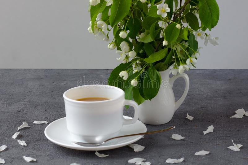 放松的时间和幸福与咖啡与在新鲜的春天花中 免版税库存照片