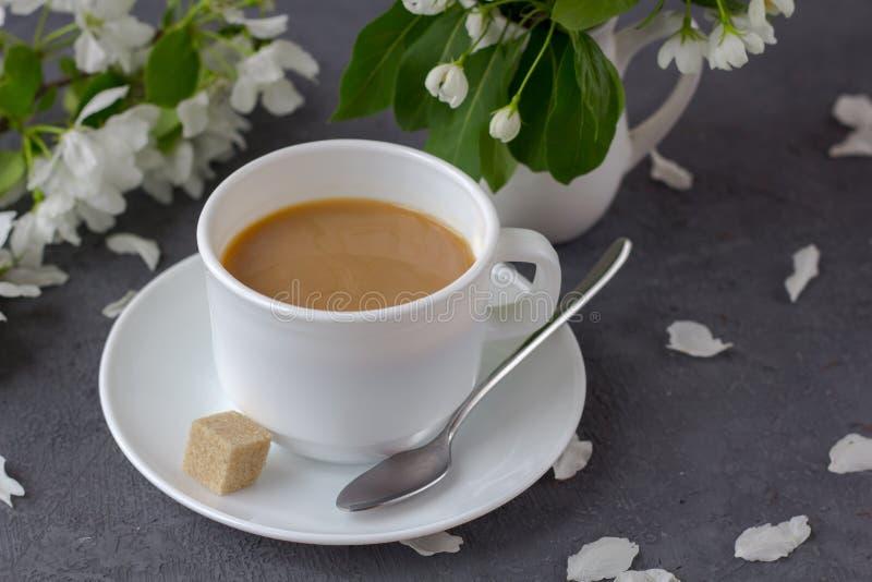 放松的时间和幸福与咖啡与在新鲜的春天花中 库存图片