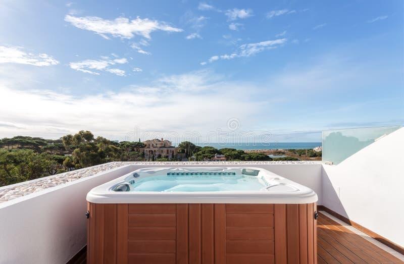 放松的极可意浴缸随员在屋顶 有海视图 免版税图库摄影