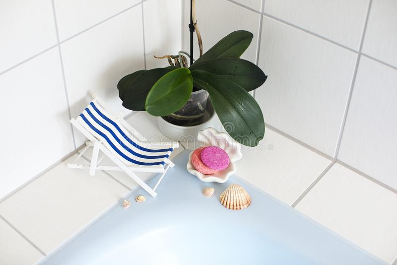 放松的葡萄酒装饰镶边海滩睡椅在游泳场或浴,贝壳,肥皂,坚实香波附近站立, 免版税库存图片