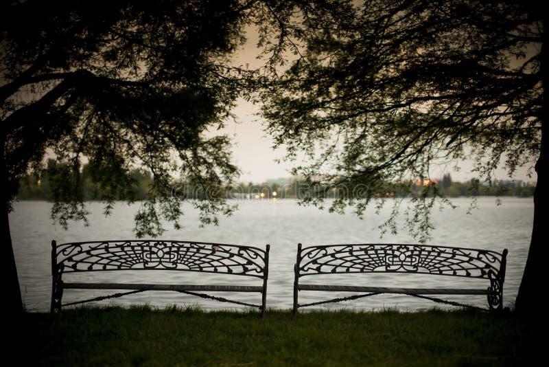 放松的长凳和湖 免版税库存照片