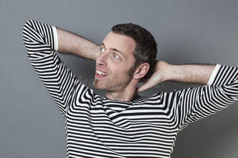 放松的40s供以人员交叉他的在他的脖子后的双臂 库存图片