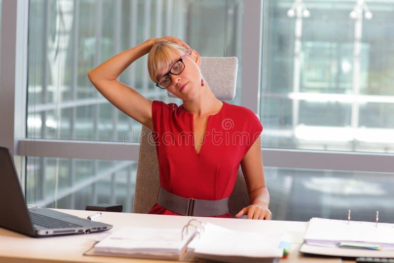 放松脖子的镜片的白种人女商人 免版税库存照片