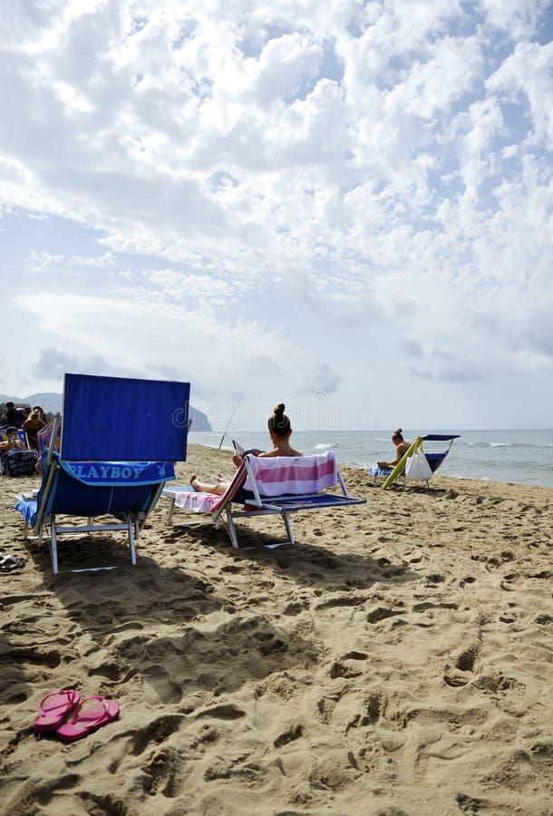 放松通过读的海滩的妇女闲话杂志 免版税图库摄影